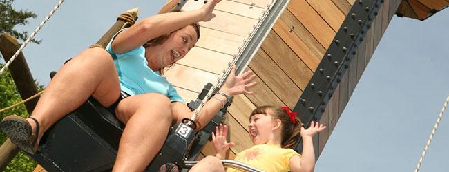 An adult and Child rising to the sky's on the Lumberjack Lifts at Dollywood wide