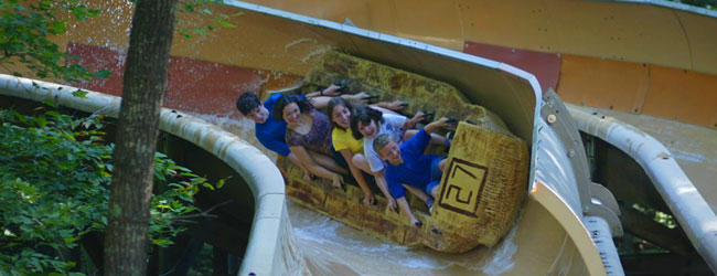 Group of kids riding in the Sled coming down the Watery Flume in the Mountain Slidewinder at Dollywood wide