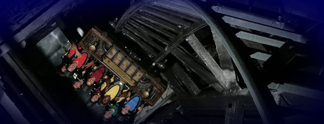 A view of the Mystery Mine Steel Roller Coaster coming out of the Mine with Car upside down at Dollywood wide